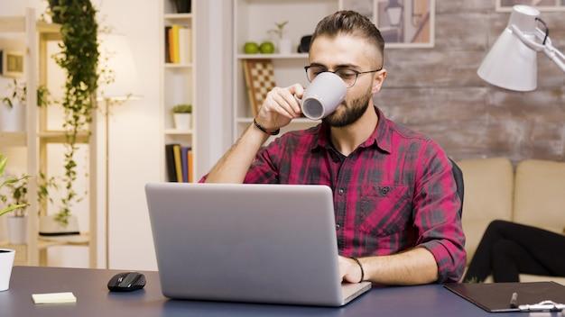 Knappe freelancer die zijn laptop opent om in de woonkamer te gaan werken. een slok koffie nemen.