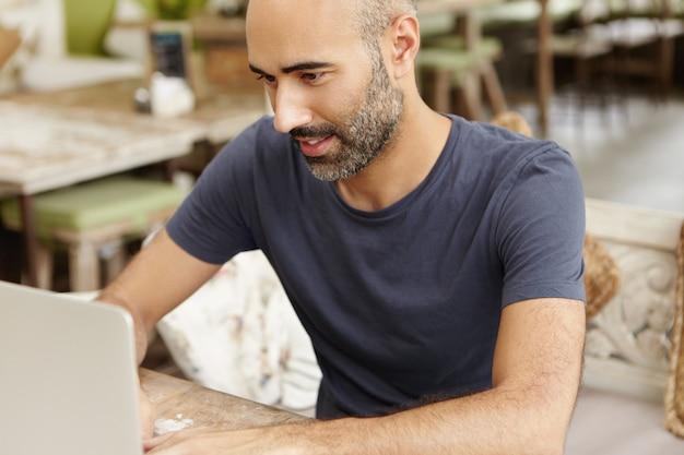 Knappe freelancer met stoppels met behulp van laptop voor extern werk, scherm kijken met gerichte expressie.