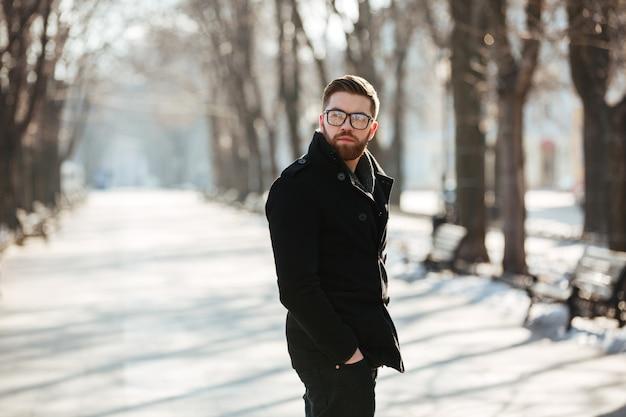 Knappe gebaarde jonge mens die zich in openlucht in de winter bevindt