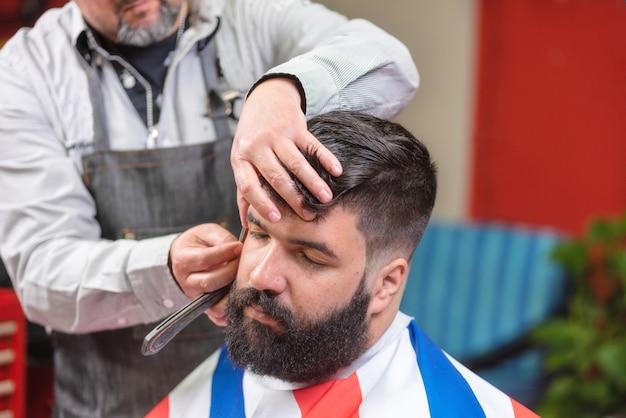 Knappe gebaarde mens die kapsel krijgen door kapper bij de kapperswinkel.