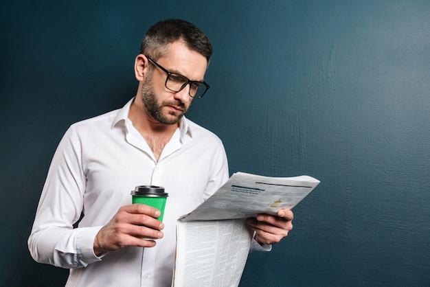 Knappe geconcentreerde mens het drinken de krant van de koffielezing.