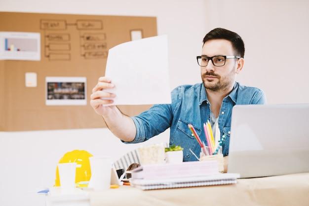 Knappe gefocuste jonge ontwerper die briefingpapier bekijkt terwijl hij aan het bureau zit.