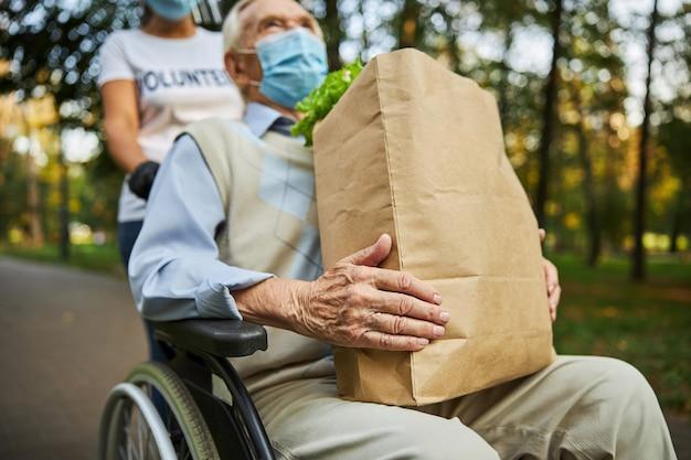 Knappe gehandicapte man in blauw shirt kijkend naar de lucht terwijl hij uitrust in het park