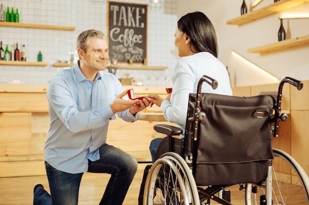 Knappe geïnspireerde blonde man die lacht en zijn geliefde donkerharige gehandicapte vrouw voorstelt en een ring vasthoudt tijdens een romantisch diner