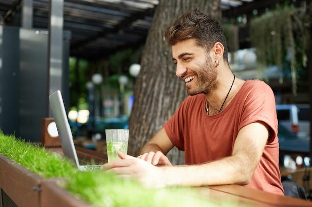 Knappe gelukkig bebaarde man in oortelefoons met laptop op terras, vrolijk glimlachend