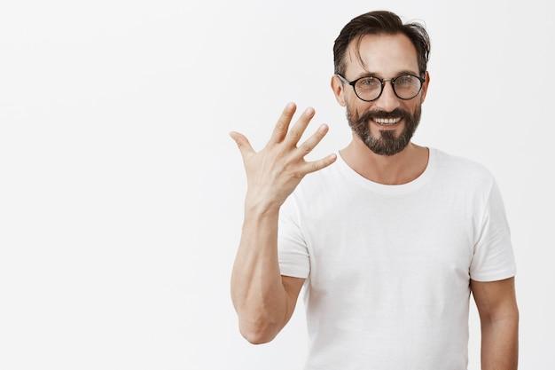 Knappe gelukkig bebaarde volwassen man met bril poseren