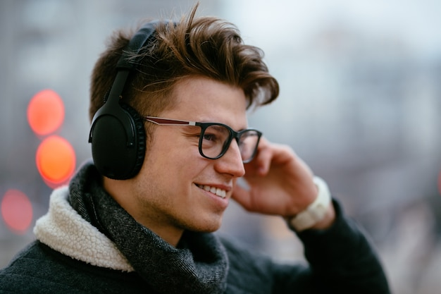 Knappe gelukkig jonge man in brillen, luisteren naar muziek in de koptelefoon