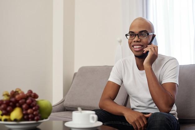 Knappe gelukkig jonge zwarte man thuis koffie drinken en praten over de telefoon met vriend of familielid