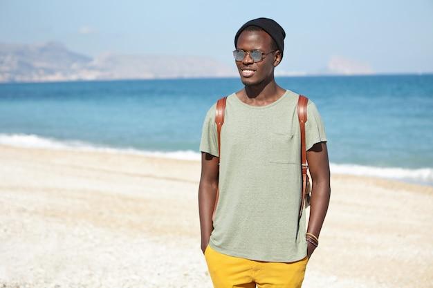 Knappe gelukkig jonge zwarte mannelijke toerist met rugzak gekleed in stijlvolle kleding staande op kiezelstrand met blauwe zee en lucht in de horizon, wachtend op vrienden om een mooie wandeling langs de kust