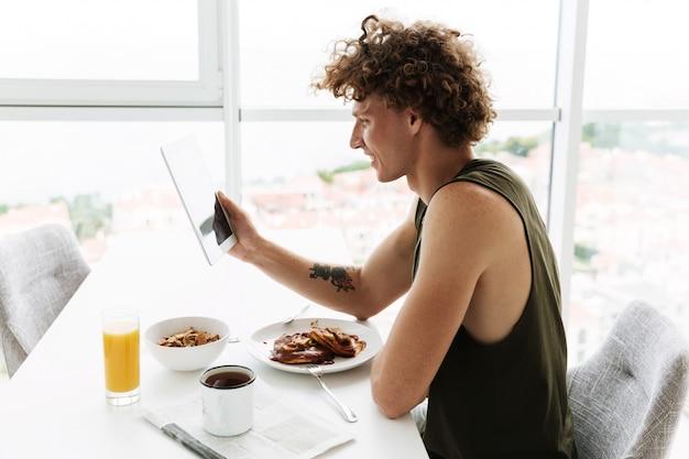 Knappe gelukkig man zit aan de keuken tijdens het gebruik van tablet
