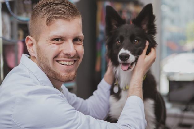 Knappe gelukkig mannelijke dierenarts lachen om de camera, schattige hond aaien op zijn kliniek