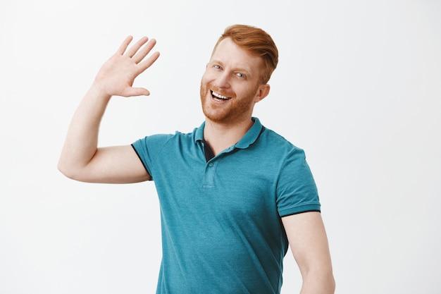 Knappe gelukkig roodharige man wacht op high five, glimlachend breed palm hoog opheffen om persoon op moderne manier te begroeten, close over grijze muur verwelkomen, trendy poloshirt dragen