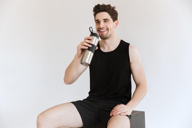 Knappe gelukkig vrolijke sterke jonge sport man drinkwater geïsoleerd.