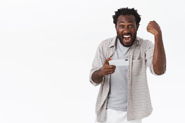 Knappe gelukkige afro-amerikaanse bebaarde man triomfeert als winstniveau, speelt smartphonespel playing