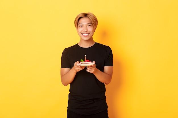 Knappe gelukkige aziatische blonde kerel, die tevreden glimlacht terwijl hij verjaardag viert, die b-dagtaart houdt, die zich over gele muur bevindt