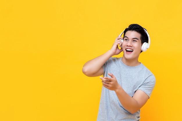 Knappe gelukkige aziatische mens die aan muziek bij hoofdtelefoons en het glimlachen luistert