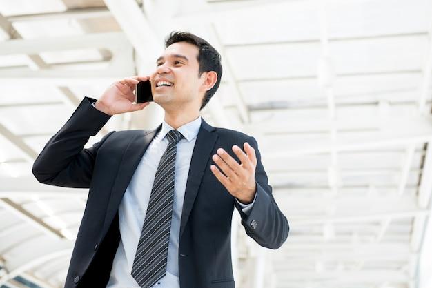 Knappe gelukkige aziatische zakenman die aan cliënt op mobiele telefoon in de stad spreekt