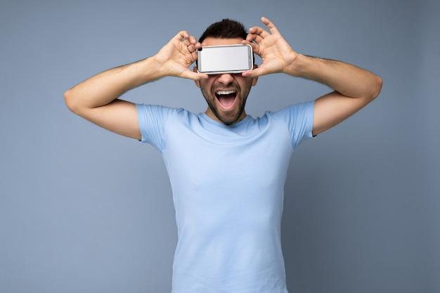 Knappe gelukkige coole jongeman die er goed uitziet met casual stijlvolle kleding die geïsoleerd staat over een kleurrijke achtergrondmuur die smartphone vasthoudt en een telefoon toont met een leeg scherm.