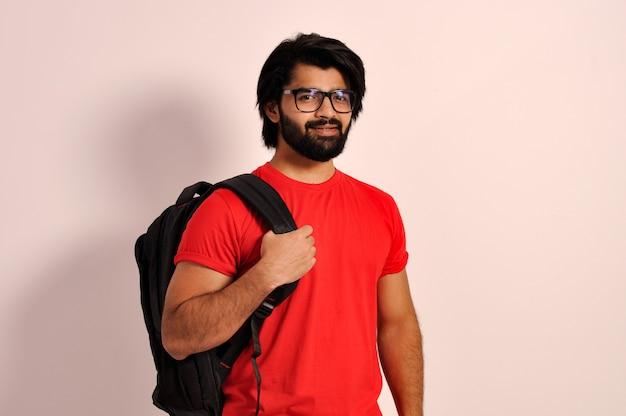 Knappe gelukkige indiase collage gaan man met rugzak en bril zelfverzekerde lachende student