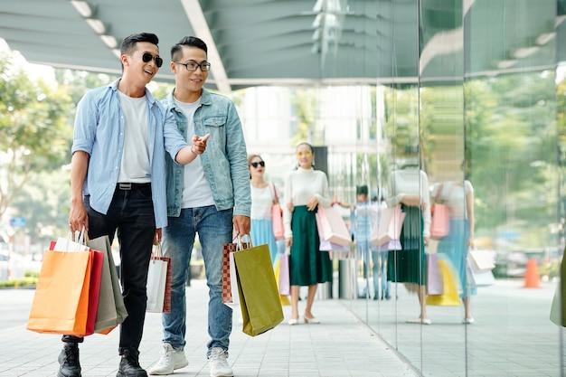 Knappe gelukkige jonge aziatische jongens genieten van samen winkelen, thay kiezen sneakers in de etalage