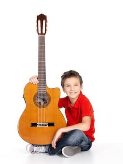 Knappe gelukkige jongen met de akoestische gitaar die op witte achtergrond wordt geïsoleerd