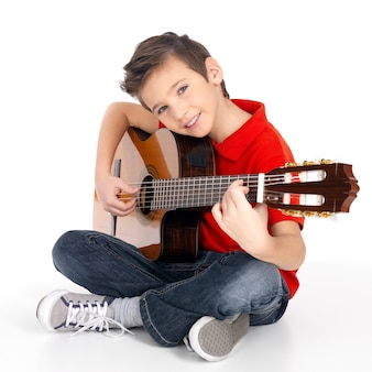 Knappe gelukkige jongen speelt op akoestische gitaar - geïsoleerd op een witte achtergrond