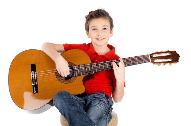Knappe gelukkige jongen speelt op akoestische gitaar op wit wordt geïsoleerd