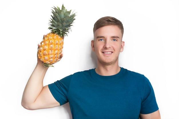 Knappe gelukkige kerel, jonge mooie man met vers rijp fruit, gele tropische ananas in de hand, glimlachend. gezonde voeding, voedsel, veganistisch of vegetarisch. love fruits concept