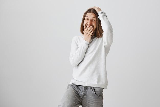 Knappe gelukkige kerel lachen om grap, oplichter mond