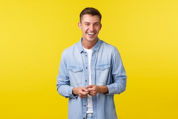 Knappe gelukkige mannelijke student in casual outfit, lachen en glimlachen, met een levendig gesprek. man kijkt vrolijk naar de camera, staat op een gele achtergrond en praat met een vriend.