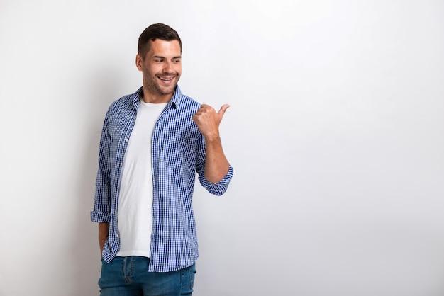 Knappe gelukkige mens die door zijn grote vinger zijdelings richt.