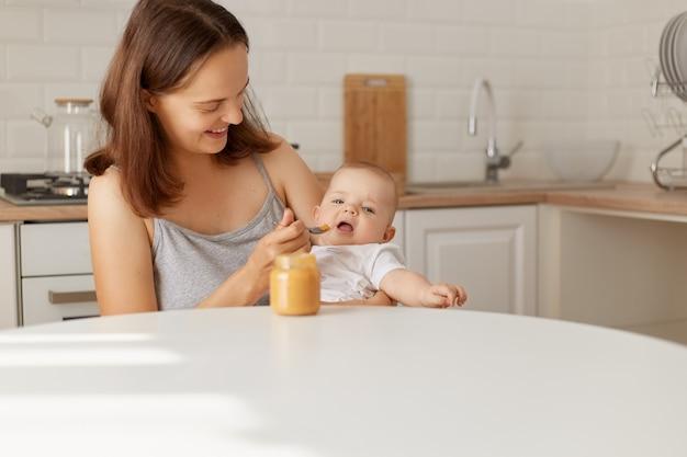 Knappe gelukkige moeder zit met dochter of zoon in handen aan tafel en voedt baby met puree uit de pot, binnenschot van mama en etend kind.
