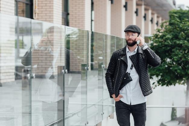 Knappe gelukkige werknemer die telefoon spreekt, koffie drinkt en 's ochtends aan het werk gaat in een modern kantoor