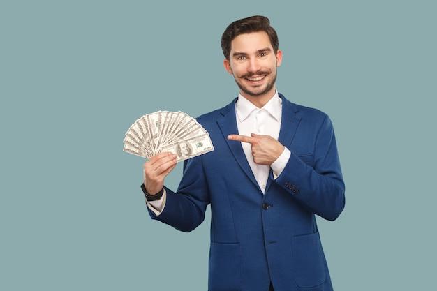 Knappe gelukkige zakenman in blauwe jas die staat en veel dollars in de hand houdt en naar de camera kijkt met een wijzende vinger en een brede glimlach. binnen, studio-opname geïsoleerd op lichtblauwe achtergrond