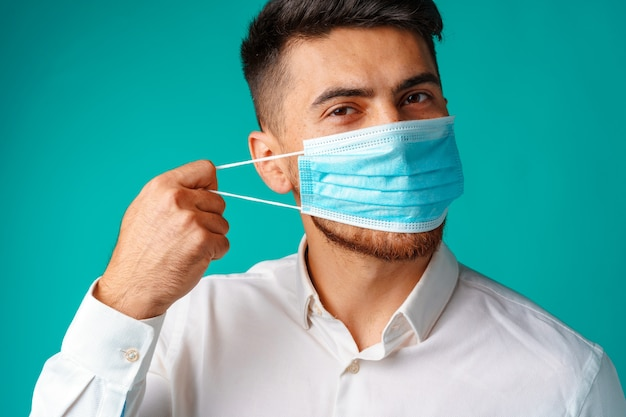 Knappe gemengde rasmens die medisch gezichtsmasker draagt