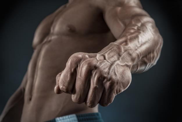 Knappe gespierde bodybuilder toont zijn vuist en ader, bloedvaten
