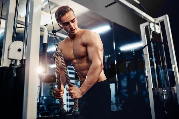 Knappe gespierde fitness bodybuilder die zware oefening voor triceps doet