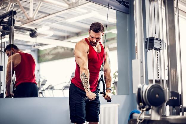 Knappe gespierde fitness bodybuilder doet zware oefening voor triceps