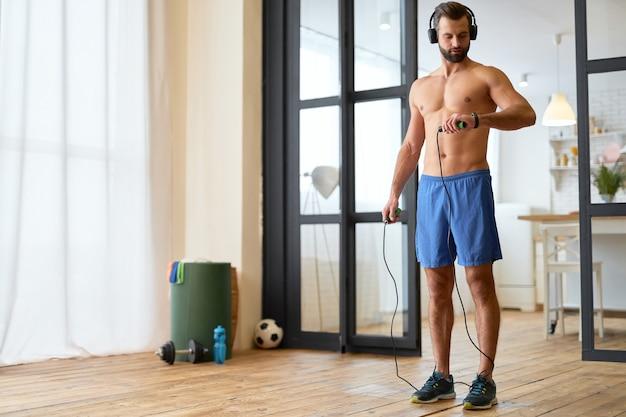 Knappe gespierde man die springtouw vasthoudt en het calorieverbruik controleert op de fitnesstracker terwijl hij naar muziek luistert via een draadloze hoofdtelefoon