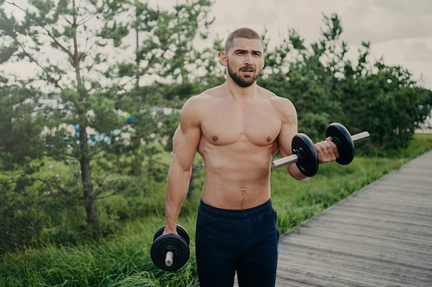 Knappe gespierde man heft halters buiten, doet biceps training