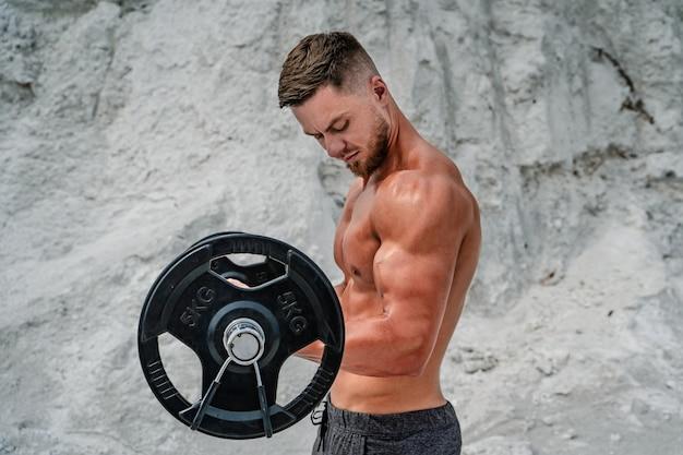 Knappe gespierde man maakt oefeningen met barbell. bodybuilding en buitensporten