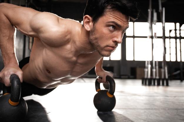 Knappe gespierde man pushup oefening met halter in een crossfit-training