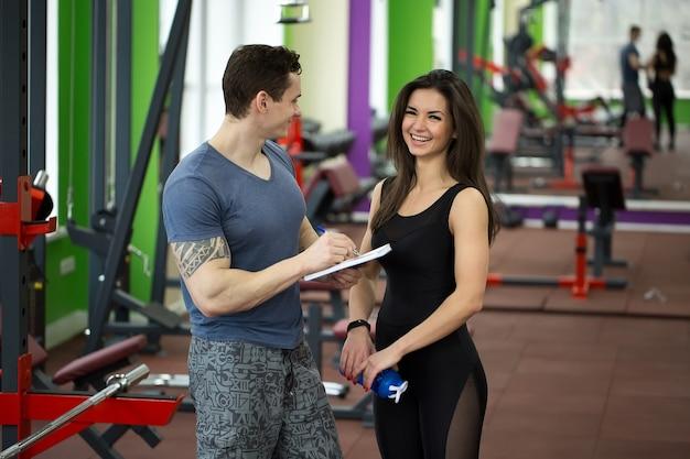 Knappe gespierde mannelijke trainer raadpleegt aantrekkelijk jong wijfje in gymnastiek die allebei glimlachen