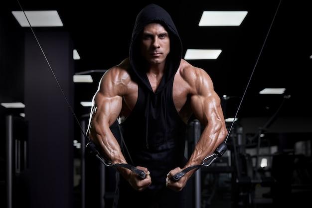 Knappe gespierde sexy man poseren in de sportschool. gelooide atleet