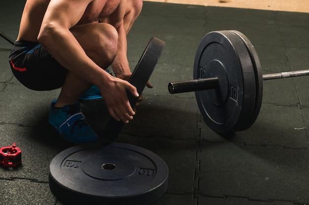 Knappe gewichtheffer die voor opleiding met barbell voorbereidingen treft