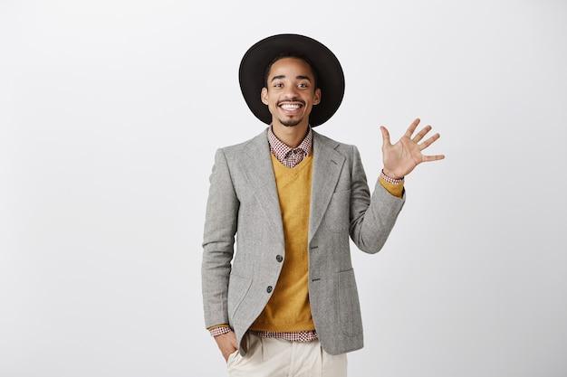 Knappe glimlachende afro-amerikaanse man in stijlvol pak met nummer vijf, bestelling maken