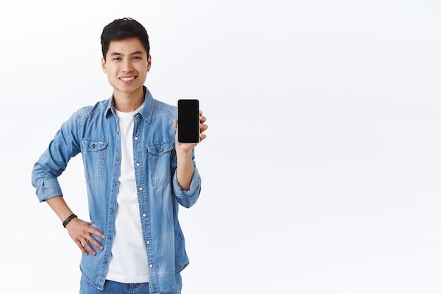 Knappe glimlachende aziatische man introduceert nieuwe applicatie, raad download-app aan of gebruik deze messenger, met display van mobiele telefoon, witte muur