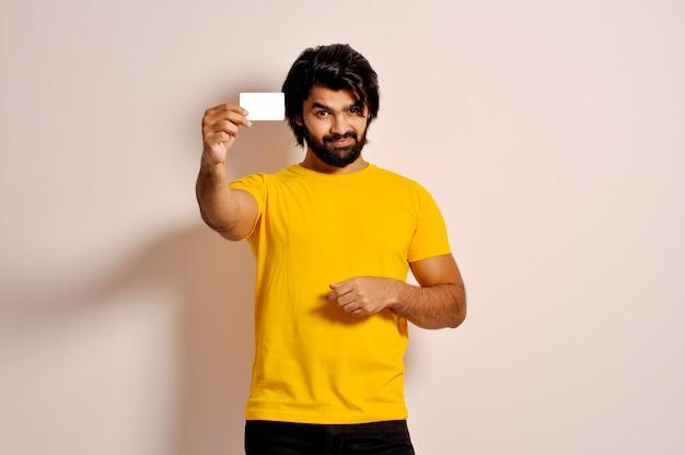 Knappe glimlachende bebaarde jonge man met gele t-shirt met creditcard die naar de camera kijkt
