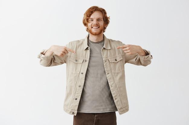Knappe glimlachende bebaarde roodharige man poseren tegen de witte muur