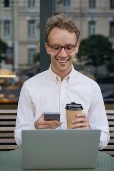 Knappe glimlachende freelancer die laptop gebruikt die mobiele telefoon houdt die koffie drinkt die online werkt